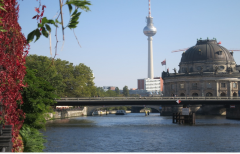 Picture of Berlin museum and TV tower from the river, with red vine leaves on the left