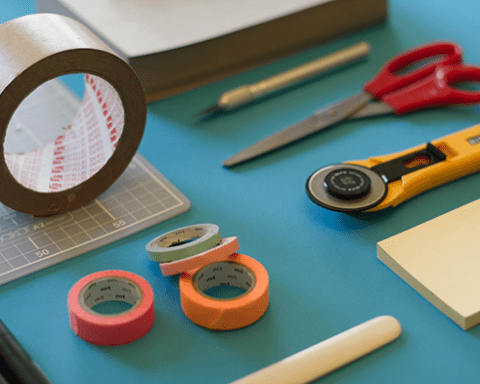 Tools like scissors, sello-tape and cutters on a blue table top